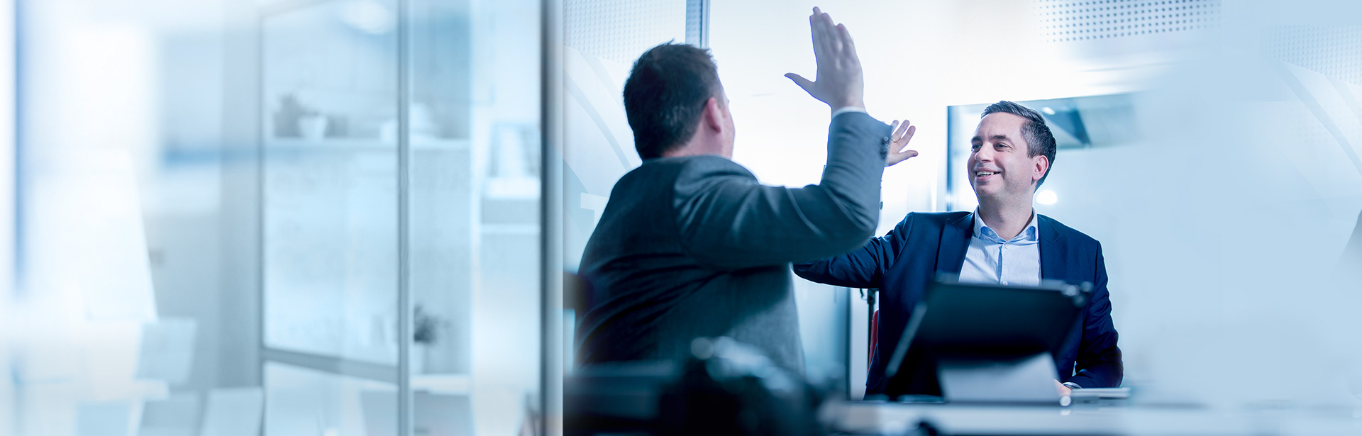 Two-men-high-five-at-office-partners-1920x615